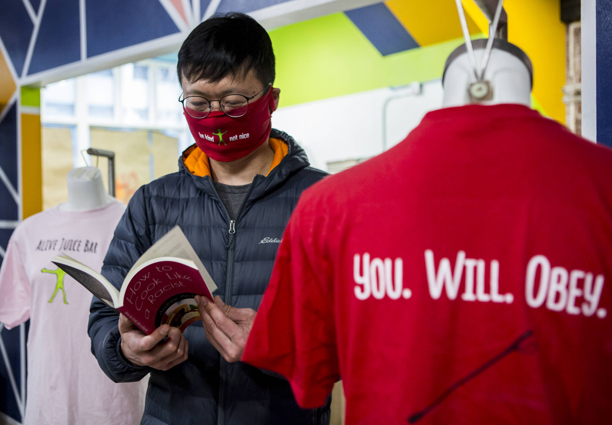 "Andrew Ho flips through his book, ""How to Cook Like A Racist,"" inside his new juice bar and soup kitchen on Wednesday in Everett. (Olivia Vanni / The Herald)"