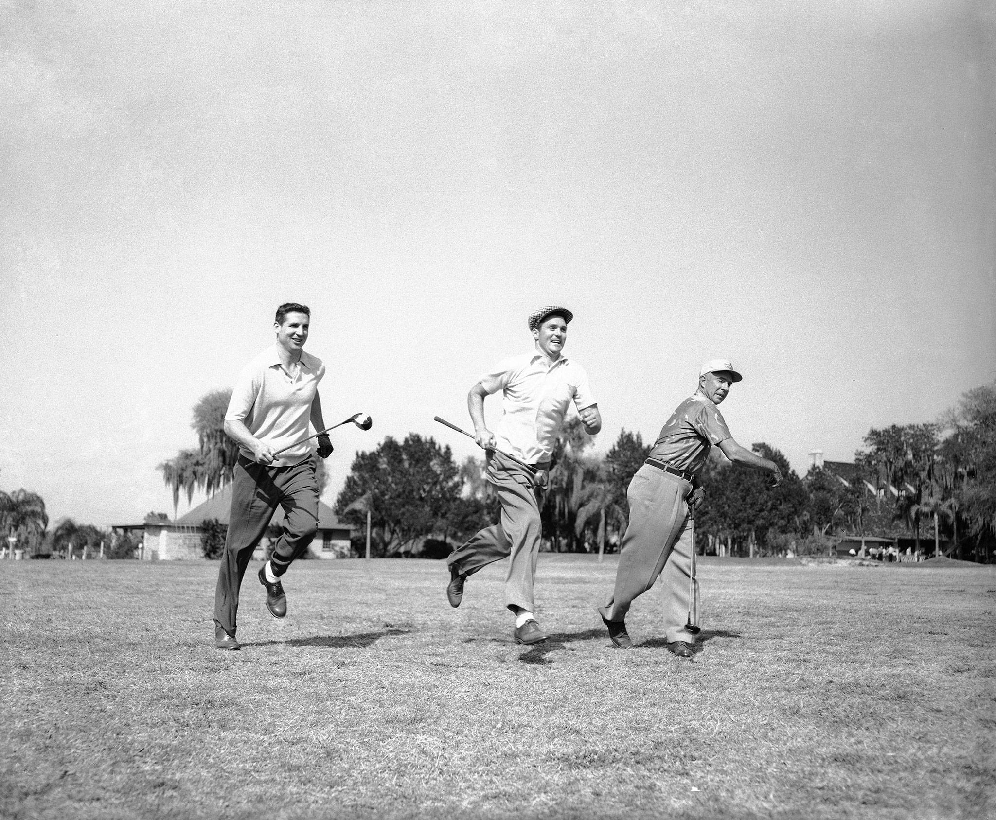 Milwaukee Braves coach Johnny Cooney (right) waves on Bobby Thomson (left) and the Phillies' Earl Torgeson (center), a Snohomish High School alum, as the players run down fairway for benefit of photographers during an annual baseball players golf tourney at Tampa Golf and Country Club in 1955. (AP Photo)