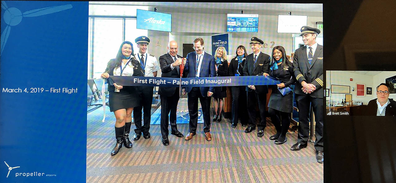 Brett Smith (right), CEO of Propeller Airports, shares a scene from the March 4, 2019 opening of the commercial airline terminal at Paine Field during a Lynnwood Chamber of Commerce virtual gathering on March 17, 2021.