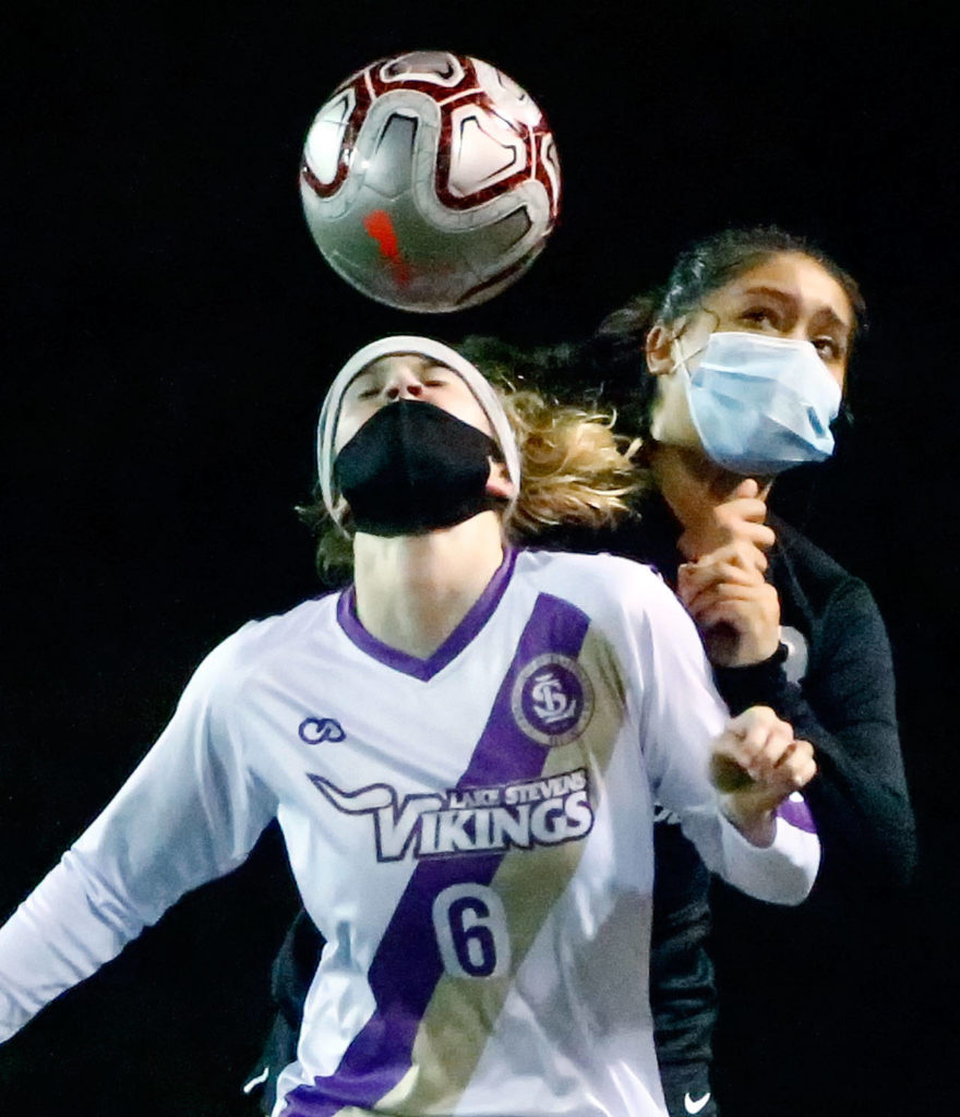 Lake Stevens' Delaine Polly heads the ball with Jackson's Maki Quiyono behind her during a March 18 game at Everett Memorial Stadium. (Kevin Clark / The Herald)