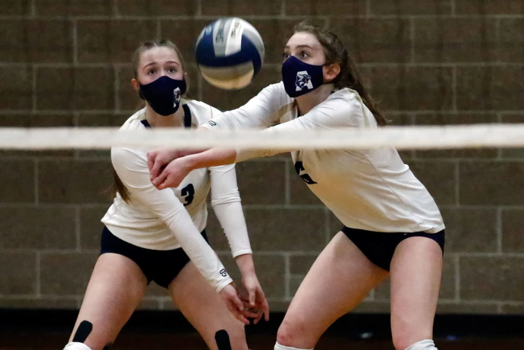 Arlington's Paige Richards (left) and Brookelynn Ramey look to dig the ball during a March 11 game against Jackson at Arlington High School. (Kevin Clark / The Herald)