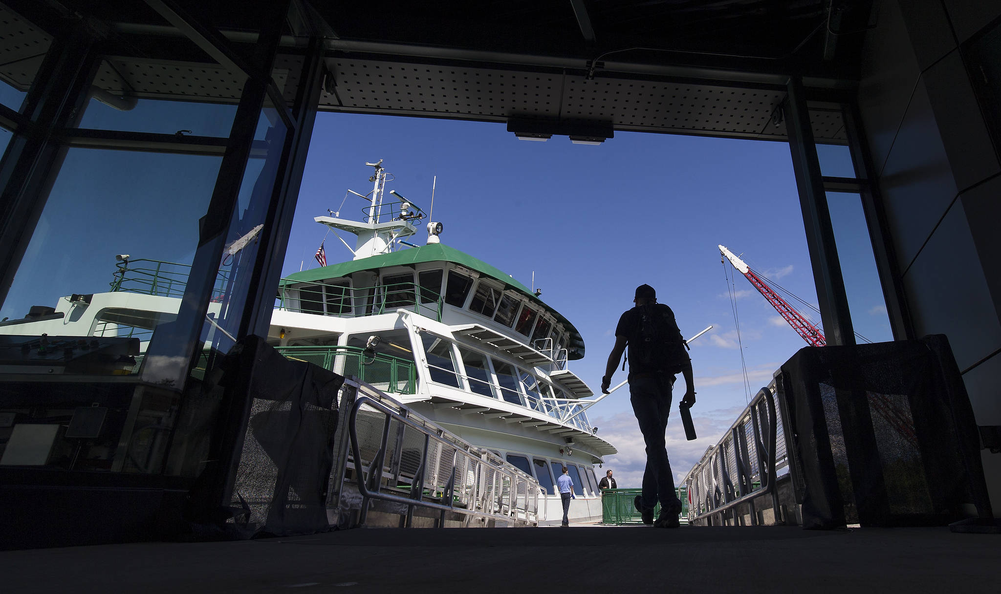 A passenger uses the overhead walkway to board a ferry at the Mukilteo terminal on Monday. It was the first day for the new service, as opposed to the previous method of boarding by way of the car deck ahead of loading cars. (Andy Bronson / The Herald)