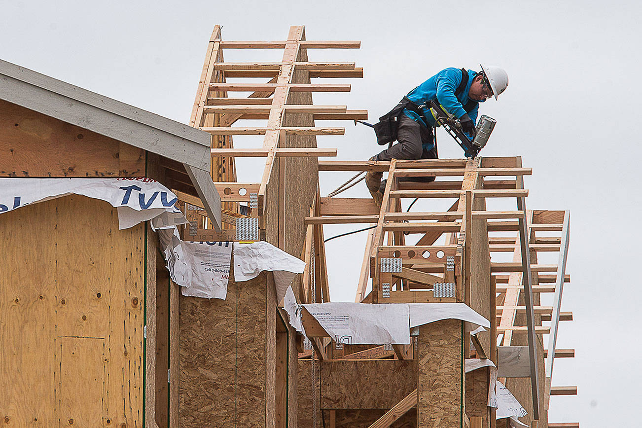 A construction worker works on the roof line of  apartments under construction in the 1600 block of E. Marine View Drive on Friday, April 24, 2020 in Everett, Wa. (Andy Bronson / The Herald)