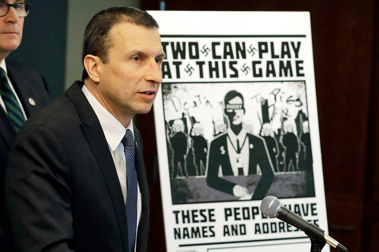 In this Feb. 26, 2020 photo, Raymond Duda, FBI Special Agent in Charge in Seattle, speaks as he stands next to a poster that was mailed earlier in the year to the home of Chris Ingalls, an investigative reporter with KING-TV during a news conference in Seattle. (AP Photo/Ted S. Warren, File)