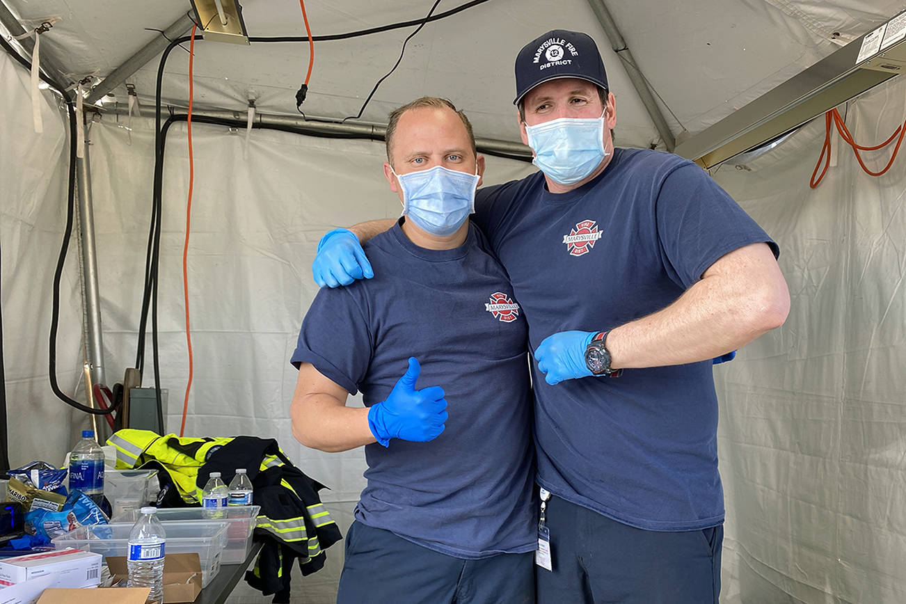 Marysville firefighters Chris Burnette (left) and Chris Lytle (right) were part of the crew vaccinating people at the Arlington Airport on Wednesday. Marysville Fire District is part of the Snohomish County Vaccine Taskforce working to get communities vaccinated. (Sue Misao / The Herald) 210331