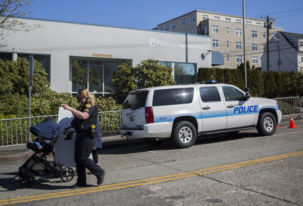 """Everett Police escort a pro-life supporter down 32nd Street in Everett on Wednesday. Barriers set up along the sidewalk around Planned Parenthood are a part of a """"time, place and manner restriction"""" imposed by the city. (Olivia Vanni / The Herald)"""