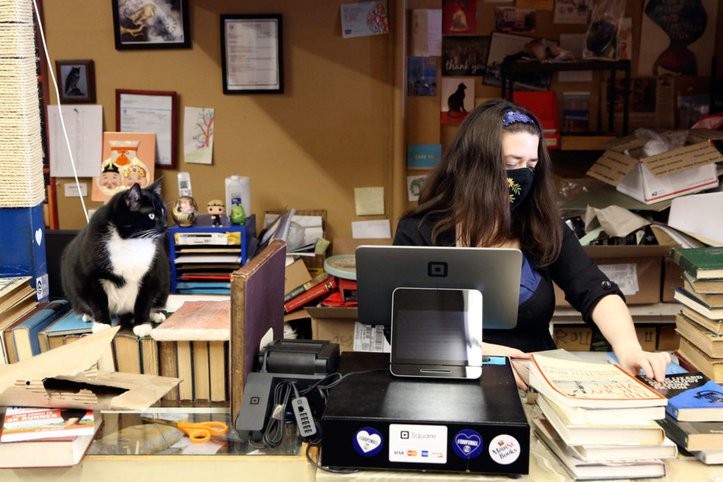Emily Newman, here with helper Miranda the cat, bought Main Street Books in Monroe in 2012. (Kevin Clark / The Herald)