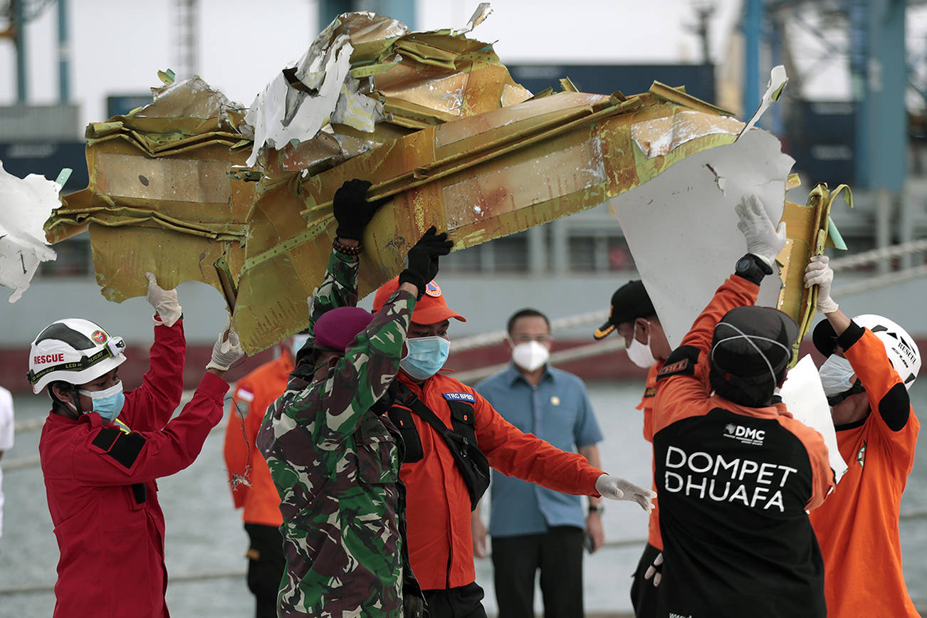 Rescuers carry a part of aircraft recovered from Java Sea where a Sriwijaya Air passenger jet crashed, at Tanjung Priok Port in Jakarta, Indonesia, Monday, Jan. 11, 2021. The search for the black boxes of a crashed Sriwijaya Air jet intensified Monday to boost the investigation into what caused the plane carrying dozens of people to nosedive at high velocity into the Java Sea. (AP Photo/Dita Alangkara)