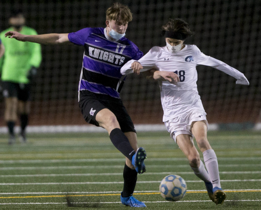 Meadowdale's Theo Uherka Hartman (right) and Kamiak's Zach Johnson go after the ball during a game on April 16, 2021, in Mukilteo. (Olivia Vanni / The Herald)