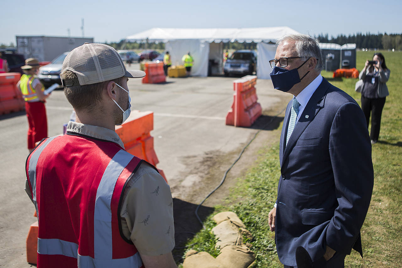 Gov. Jay Inslee speaks with pod manager Peyton Plucker at the mass COVID-19 vaccination site at the Arlington Municipal Airport on Tuesday. On Thursday, the governor said Washington state has entered its fourth wave of the pandemic. (Olivia Vanni / The Herald)