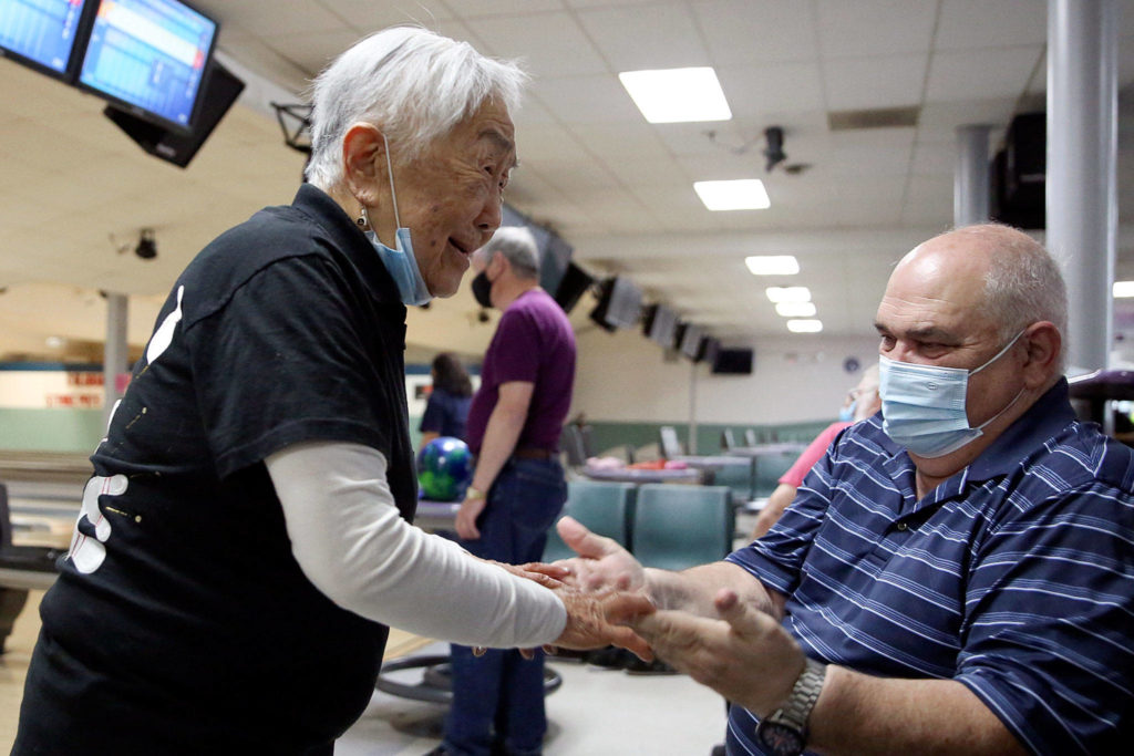 Mae Tomita (left) celebrates with Richard Steele after picking up a spare in the first frame Wednesday afternoon at Strawberry Lanes in Marysville. (Kevin Clark / The Herald)