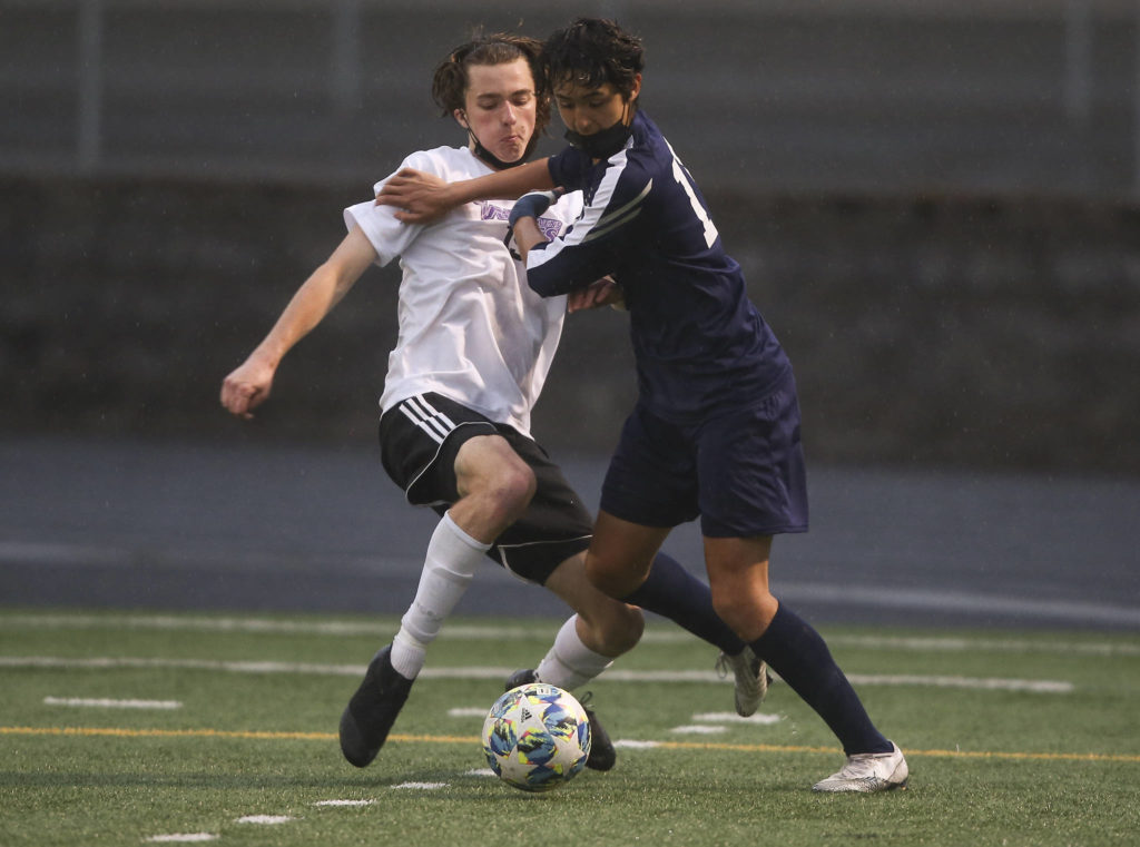 Lake Stevens' Jordan Ross and Arlington's Gio Castillo battle for the ball as Arlington beat Lakes Stevens 2-1 in a boys soccer match on Monday, May 3, 2021 in Arlington, Washington. (Andy Bronson / The Herald)