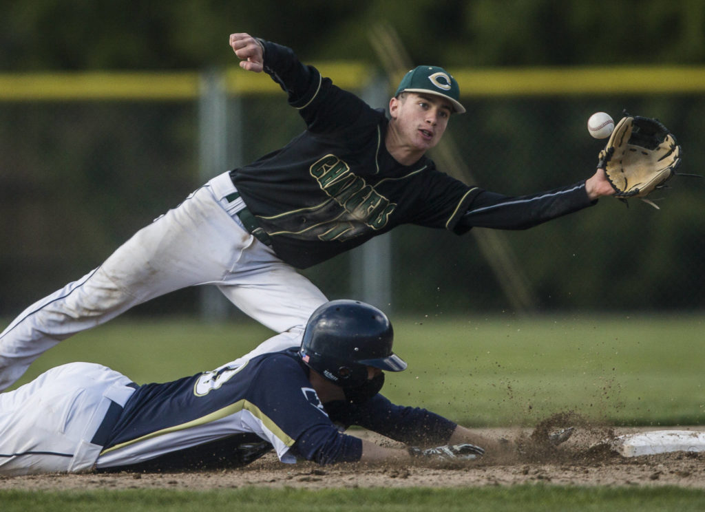 Marysville Getchell's Ethan Jury top reaches out for the ball as Arlington's Nick Salstrom dives back to second base during a game on May 7, 2021, in Arlington. (Olivia Vanni / The Herald)