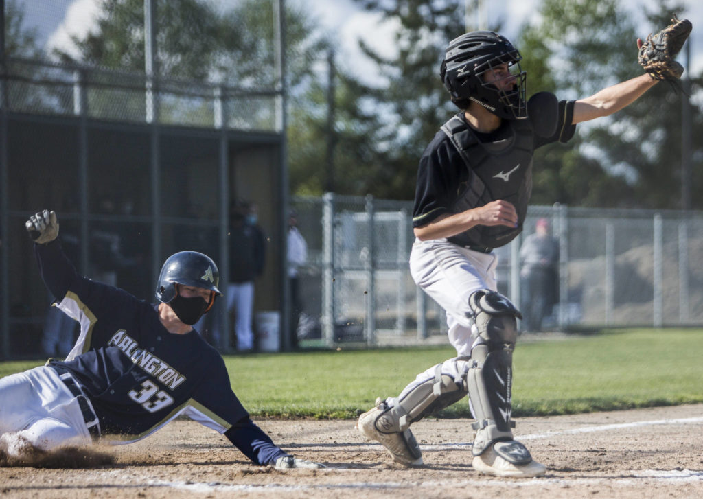 Arlington's Nick Salstrom slides into home to score during a game against Marysville Getchell on May 7, 2021, in Arlington. (Olivia Vanni / The Herald)