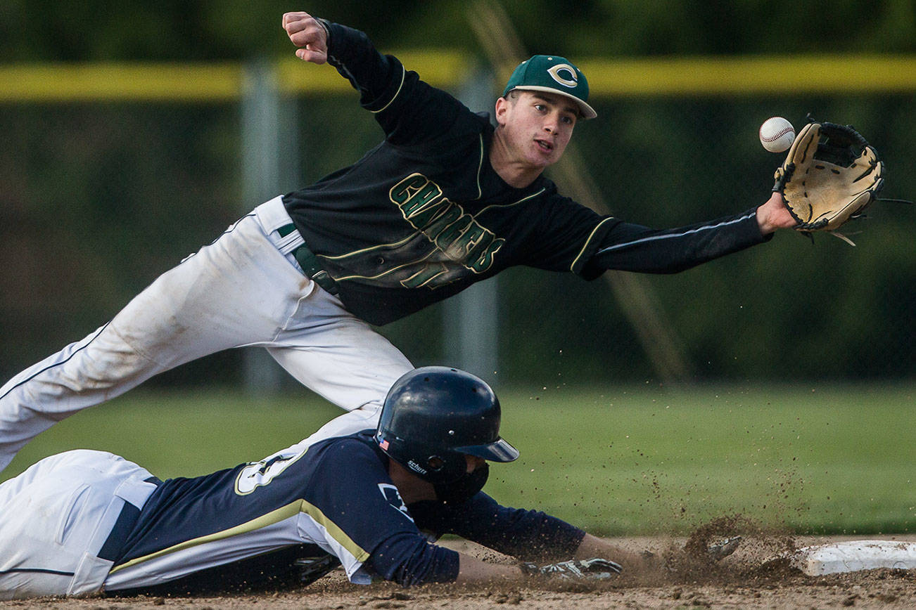 Marysville Getchell's Ethan Jury reaches out for the ball as Arlington's Nick Salstrom dives back to second base during the game on Friday, May 7, 2021 in Arlington, Wash. (Olivia Vanni / The Herald)