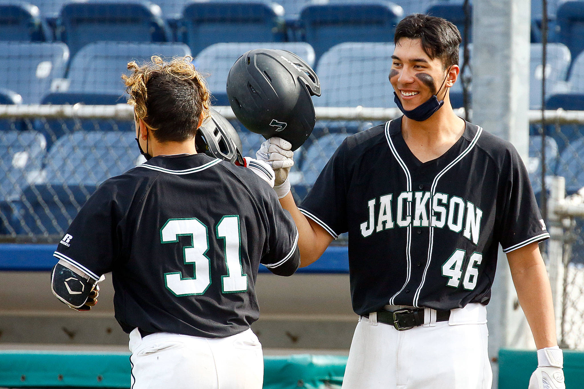 Jackson's Ryan Contreras is welcomed by teammate Dominic Hellman after Contreras' home run Friday afternoon at Funko Field at Memorial Stadium in Everett on April 23, 2021. (Kevin Clark / The Herald)