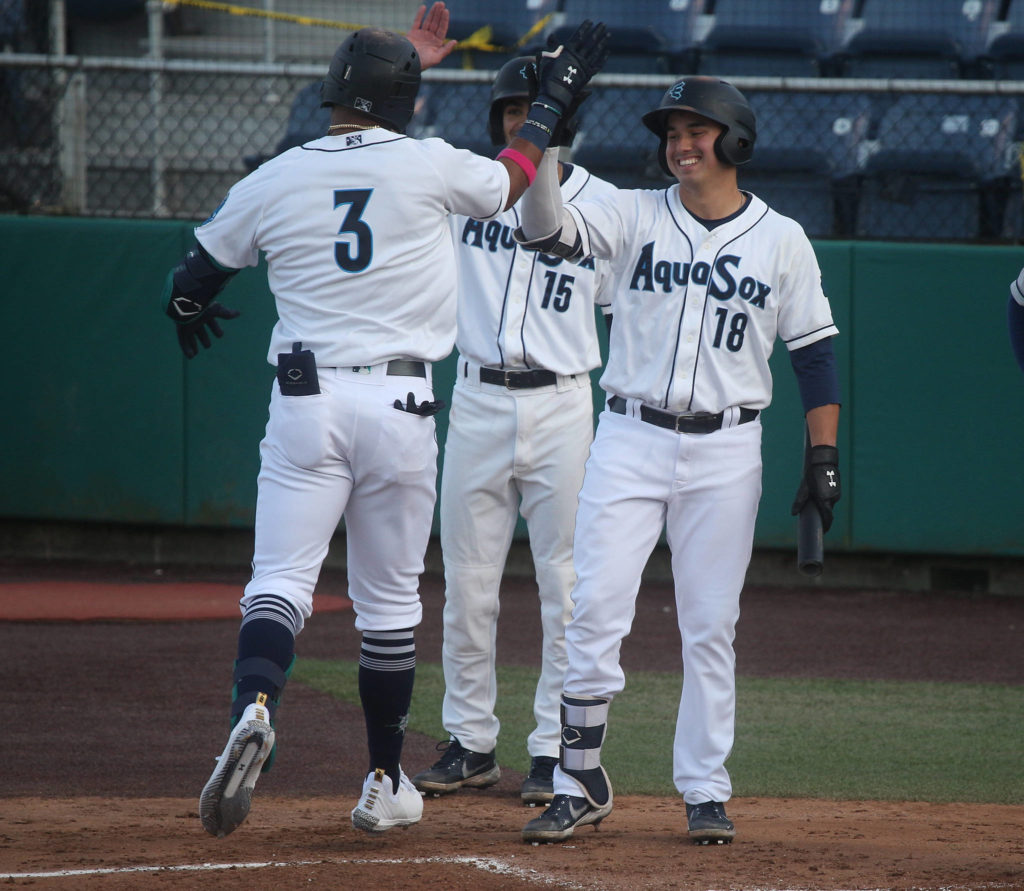 Aquasox's Julio Rodriguez gets a high five from Austin Shelton as he crosses home plate after hitting a two-run homer. The Everett Aquasox beat the Tri-City Dust Devils in a home opening game at Funko Field on Tuesday, May 11, 2021 in Everett, Washington. (Andy Bronson / The Herald)