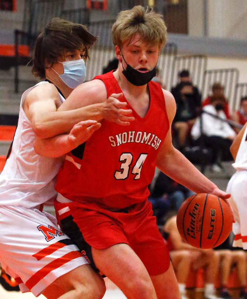 Snohomish's Grady Kentch controls the ball Monroe's Ryan Lynch defending during a game on May 11, 2021, at Monroe High School. The Bearcats won 36-35. (Kevin Clark / The Herald)