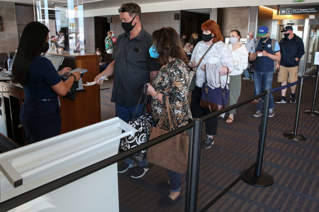 Passengers line up to board a flight to Las Vegas Wednesday afternoon at Paine Field in Everett. (Kevin Clark / The Herald)