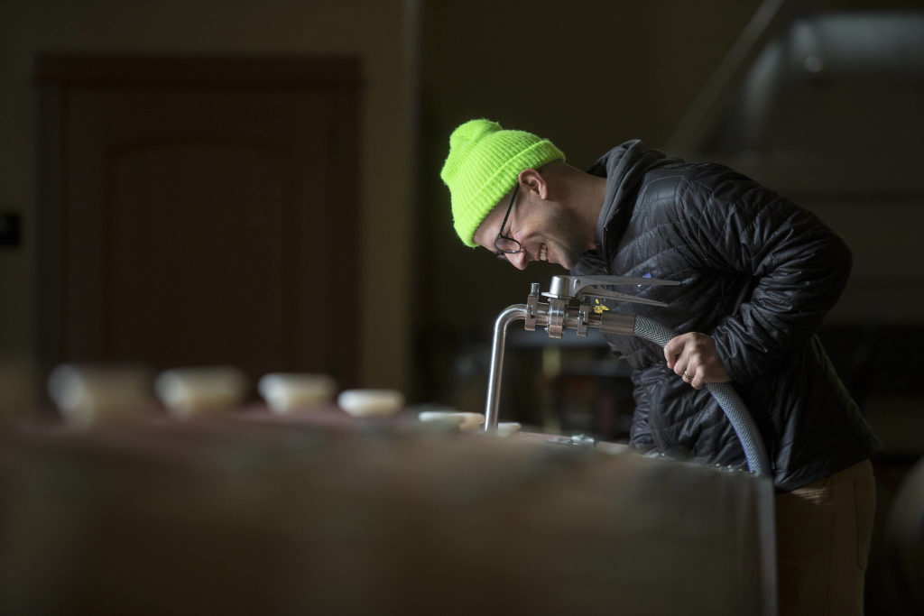 Winemaker Alex Stewart fills barrels with Columbia Valley Red at Quilceda Creek on Monday, May 17, 2021 in Snohomish, Washington. (Andy Bronson / The Herald)