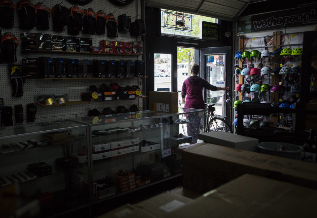 A customer walks out with their bike Friday after getting it serviced at Tim's Bike Shop in Everett. The pandemic has been good, if stressful, for bike shops across the county. (Olivia Vanni / The Herald)