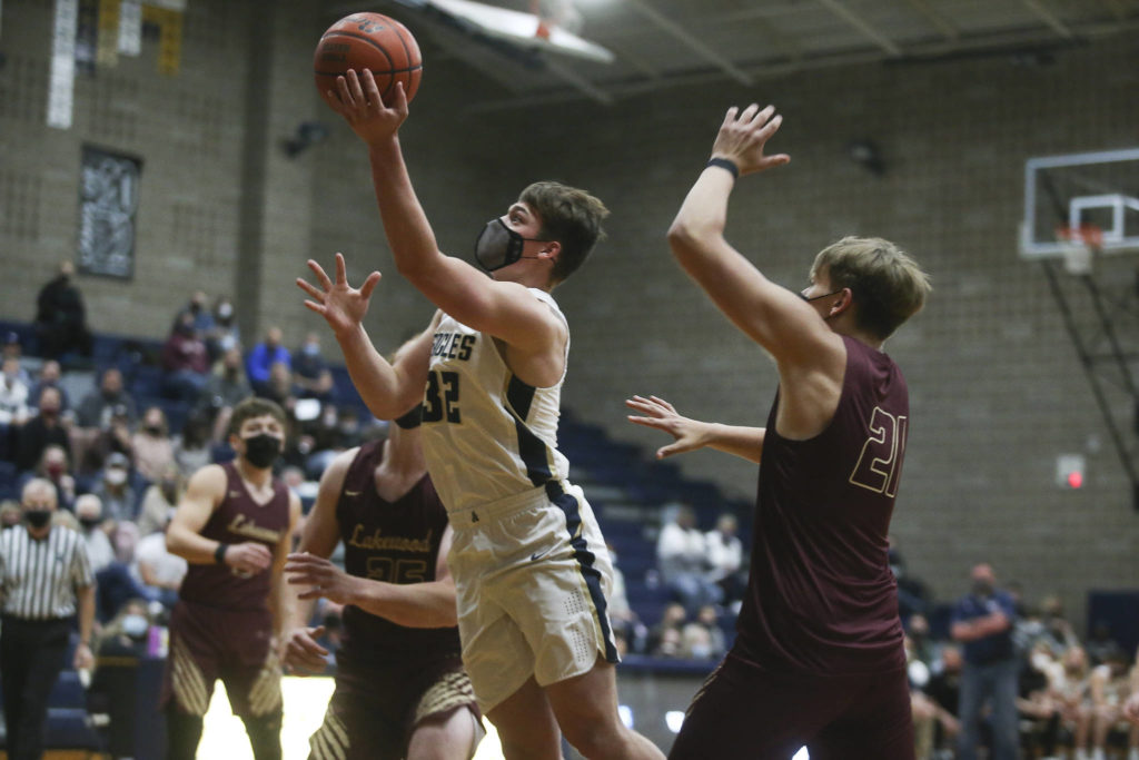 Arlington's Jaden Roskelley shoots over Lakewood's Andrew Molloy for a basket during a game on May 19, 2021, in Arlington. (Andy Bronson / The Herald)