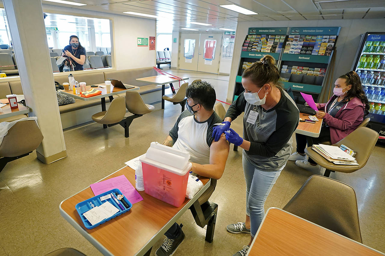 Amber Coole (right), a medical assistant with Peninsula Community Health Services, gives Omar Rodas (left) the first shot of the Pfizer COVID-19 vaccine Tuesday in the galley area of a Washington state ferry sailing from Bremerton to Seattle. (AP Photo/Ted S. Warren)