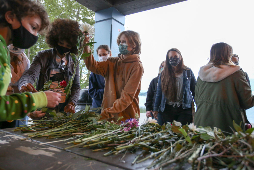 People gather flowers for the one-year anniversary of the death of George Floyd at Lundeen Park in Lake Stevens on Tuesday. (Kevin Clark / The Herald)