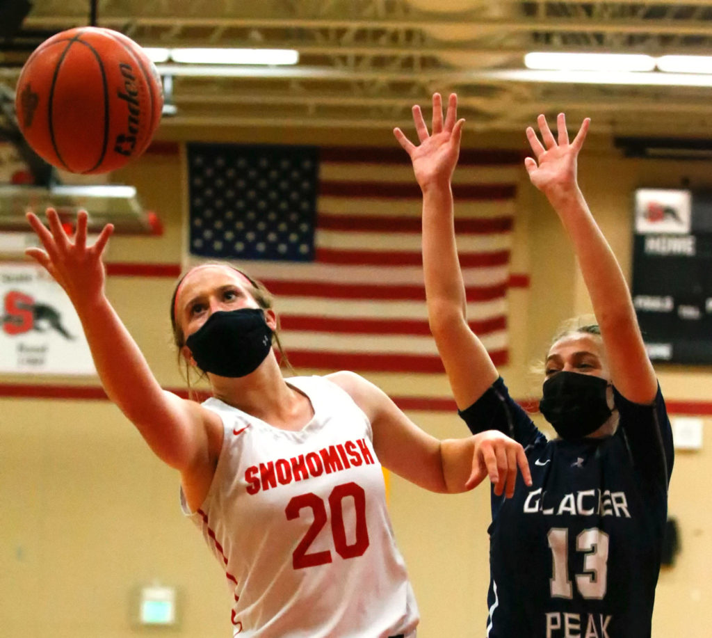 Snohomish's Sara Rodgers reaches for a rebound with Glacier Peak's Hailey Stevenson during a game on Friday evening at Snohomish High School. Grizzlies won 59-35. (Kevin Clark / The Herald)