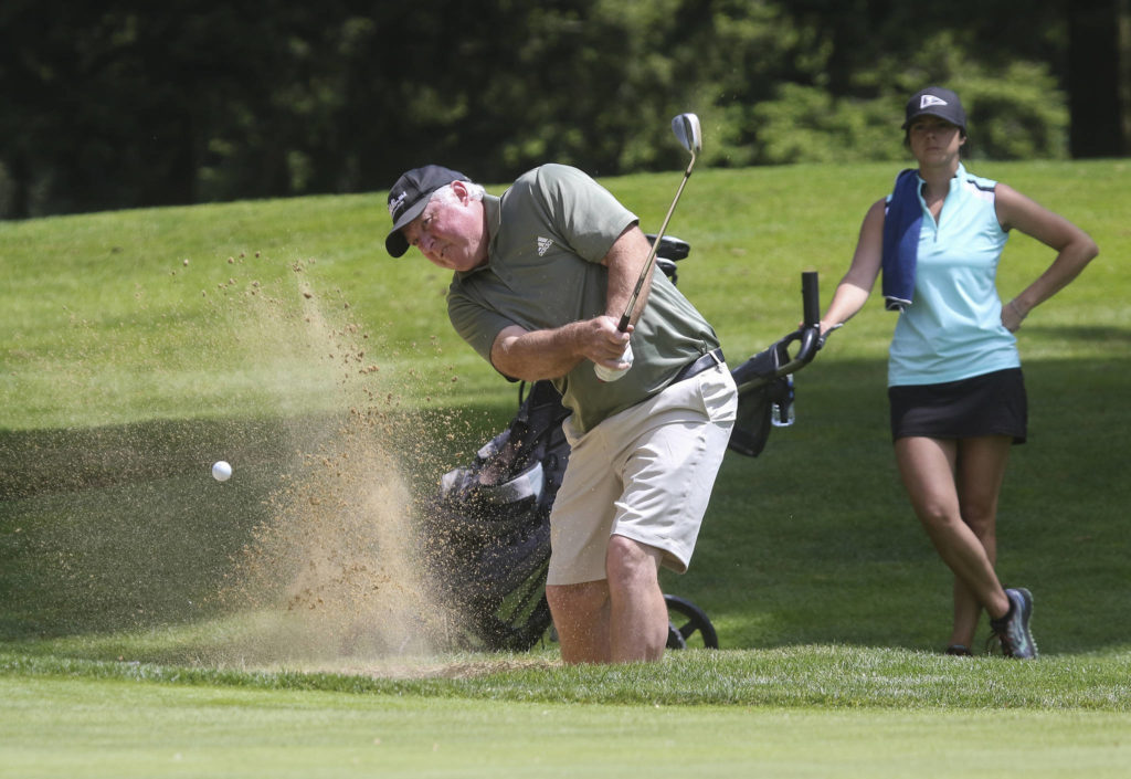 Greg Whisman hits out of a bunker. (Andy Bronson / The Herald)