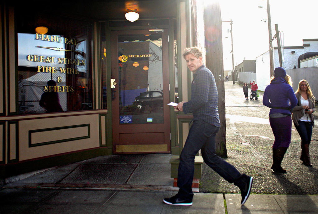 """Celebrity chef Gordon Ramsay hurriedly walks into the Prohibition Grille on Dec. 5, 2012 while filming an episode of """"Kitchen Nightmares"""" to makeover the struggling downtown Everett restaurant. (Mark Mulligan / The Herald)"""