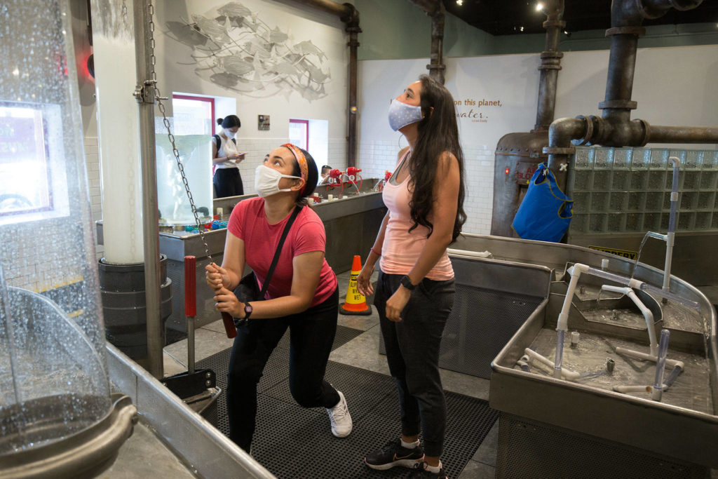 Even adults get in on the fun as Janet Ruiz (left) pulls on a chain releasing a funnel of water and Lina Forero sees the reaction at Imagine Children's Museum on Wednesday in Everett. (Andy Bronson / The Herald)