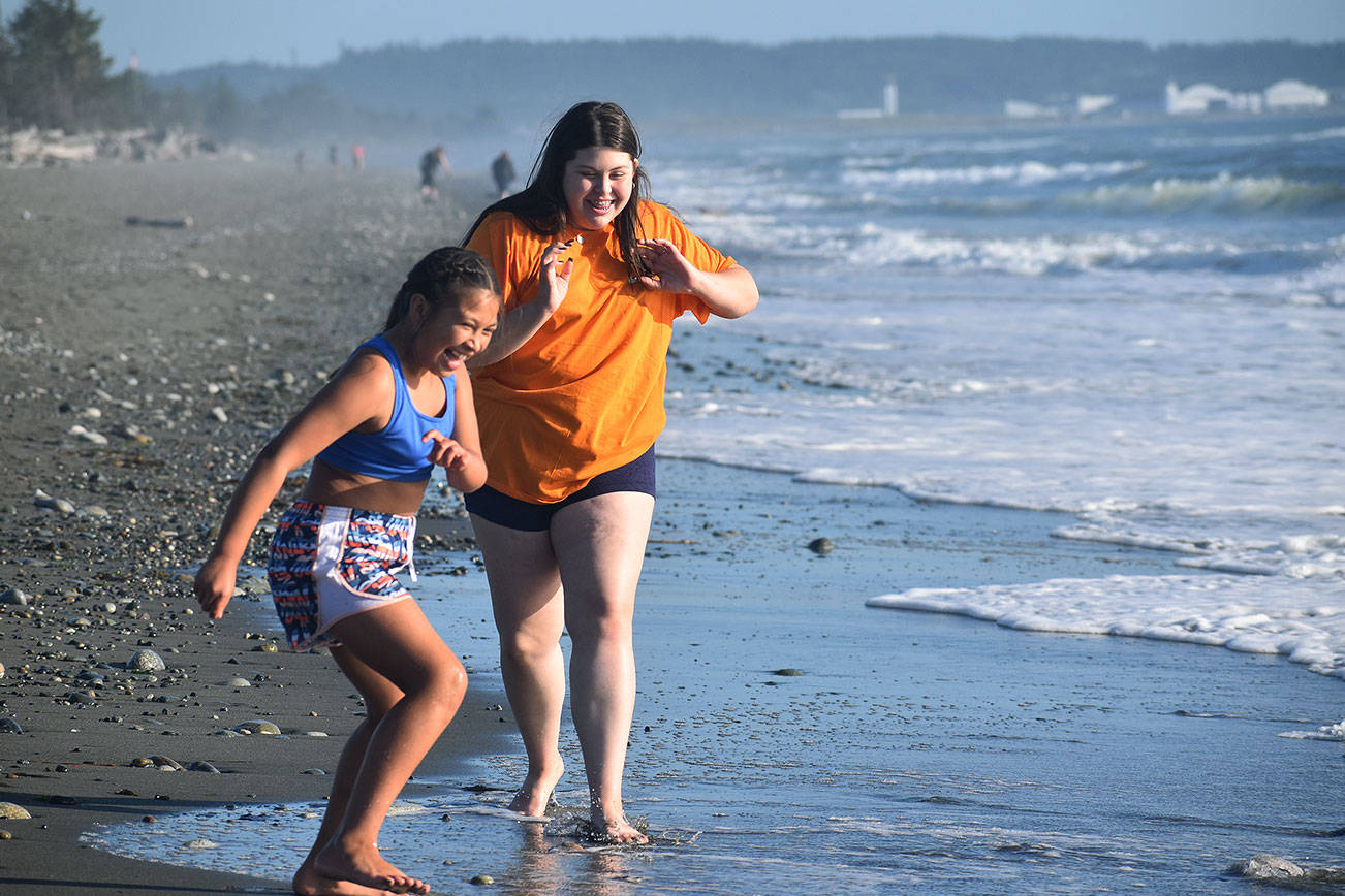 Photo by Emily Gilbert/Whidbey News-Times Caraleigh Hernandez, 10, left, and her sister Denelle, 14, play on the beach at Deception Pass State Park.
