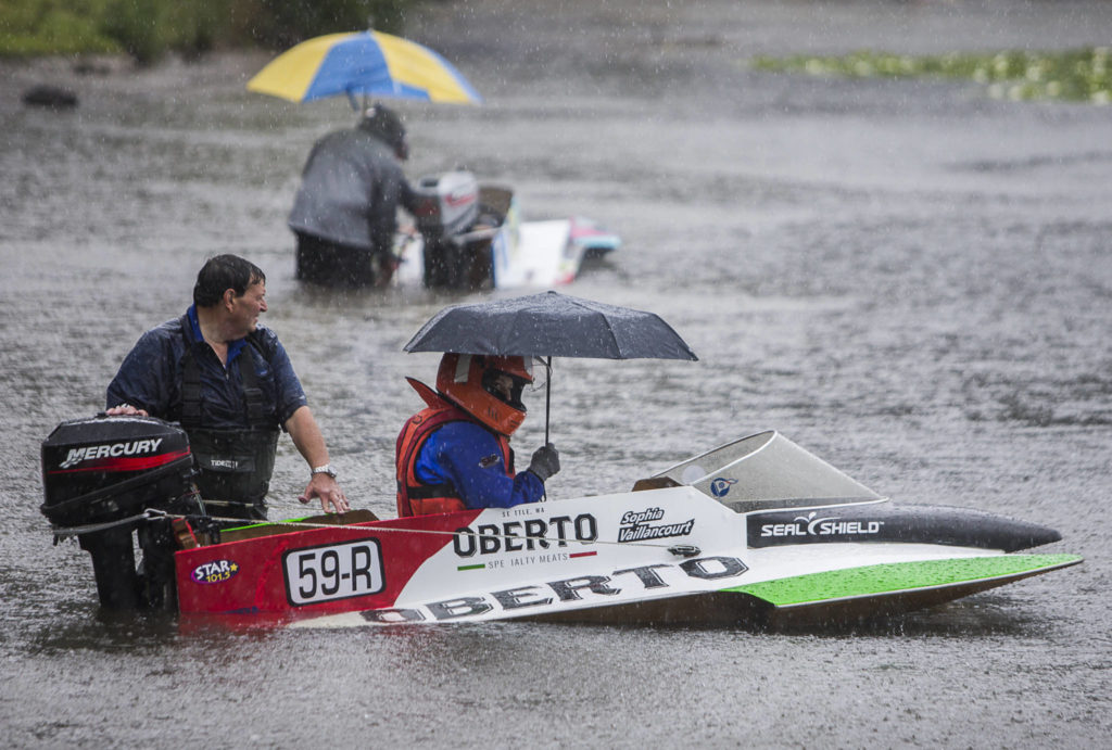 Sophia Vaillancourt sits in her mini hydroplane under an umbrella while her father, Dave Vaillancourt, holds her boat in place as they wait for her race to be announced on Saturday, June 5, 2021 in Everett, Wash. (Olivia Vanni / The Herald)