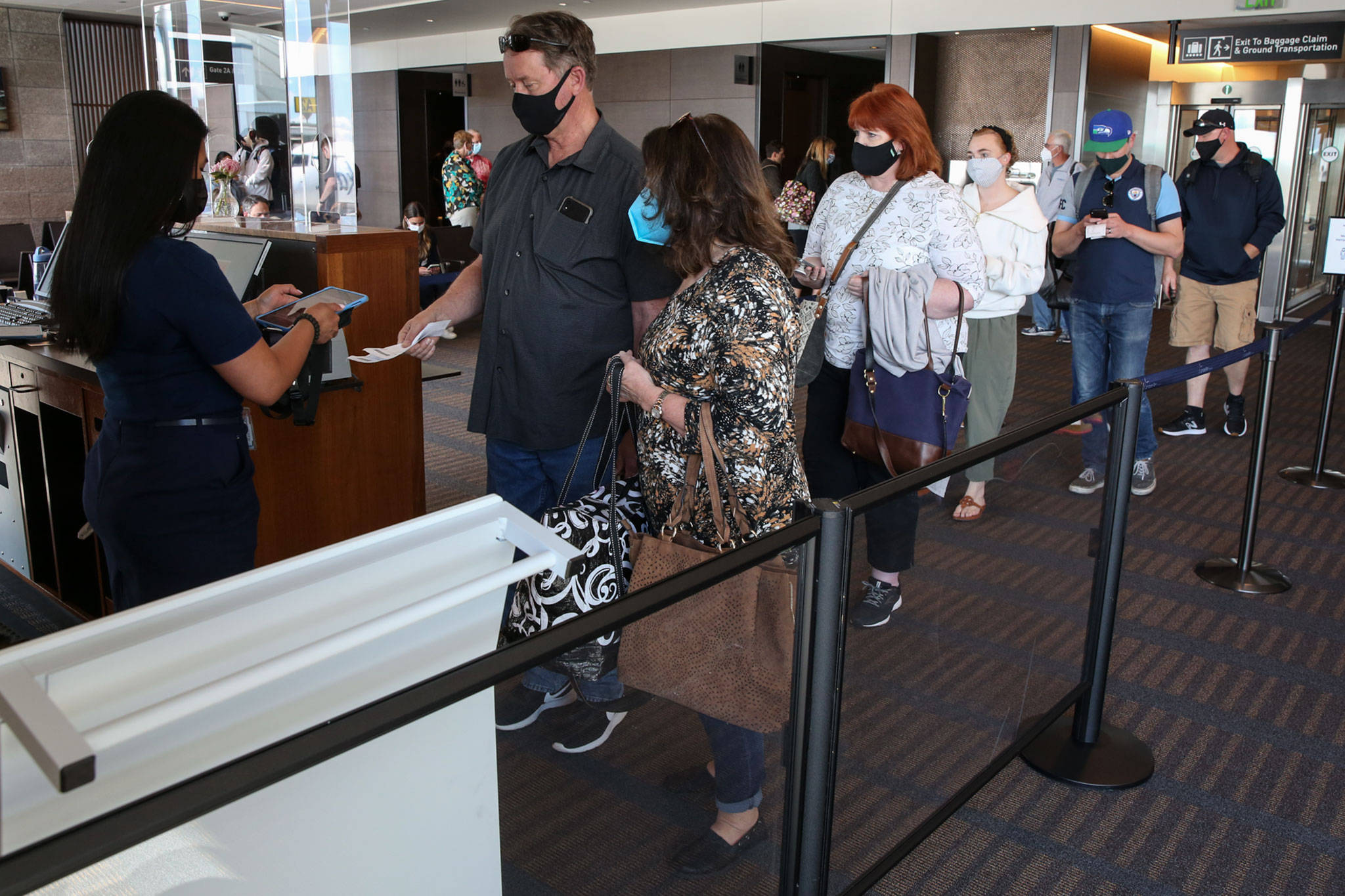 Passengers line up to board a flight to Las Vegas at Paine Field in Everett on May 19. (Kevin Clark / Herald file)