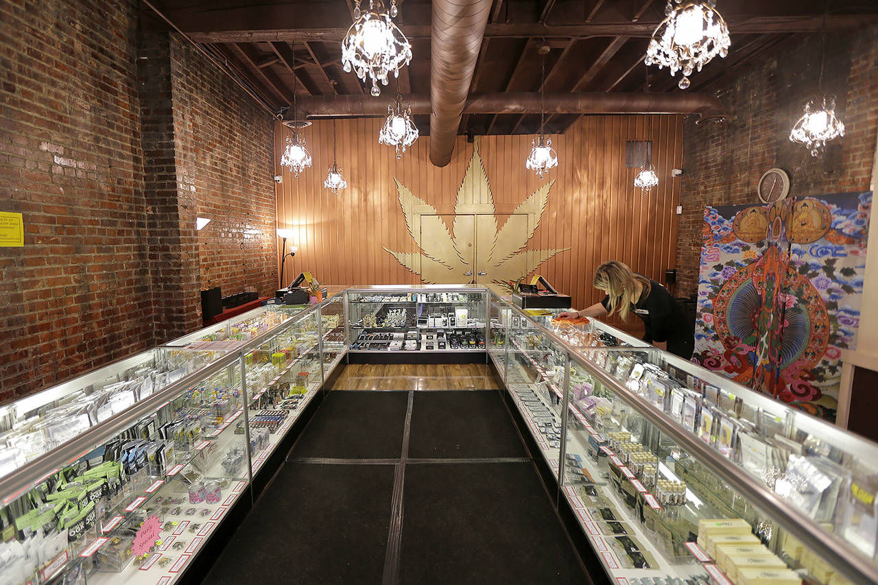 In this 2015 photo, a worker cleans a display case at the Ganja Goddess Cannabis Store in Seattle. (AP Photo/Ted S. Warren, File)