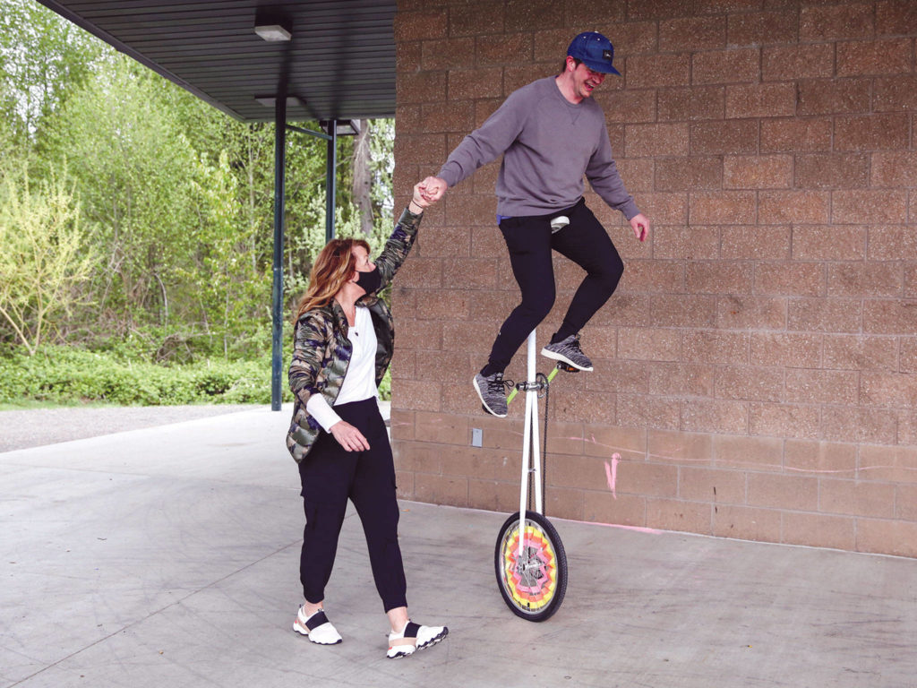 """Toni Munizza helps Nate Feltner ride the """"giraffe"""" unicycle. (Kevin Clark / The Herald)"""