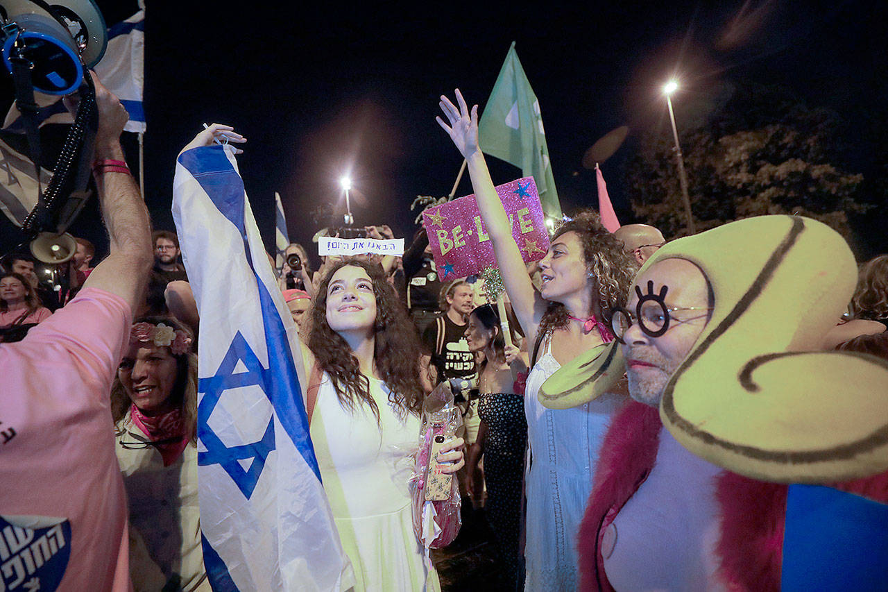 Israelis celebrate the swearing in of the new government in Jerusalem on Sunday. Israel's parliament has voted in favor of a new coalition government, formally ending Prime Minister Benjamin Netanyahu's historic 12-year rule. (AP Photo/Sebastian Scheiner)