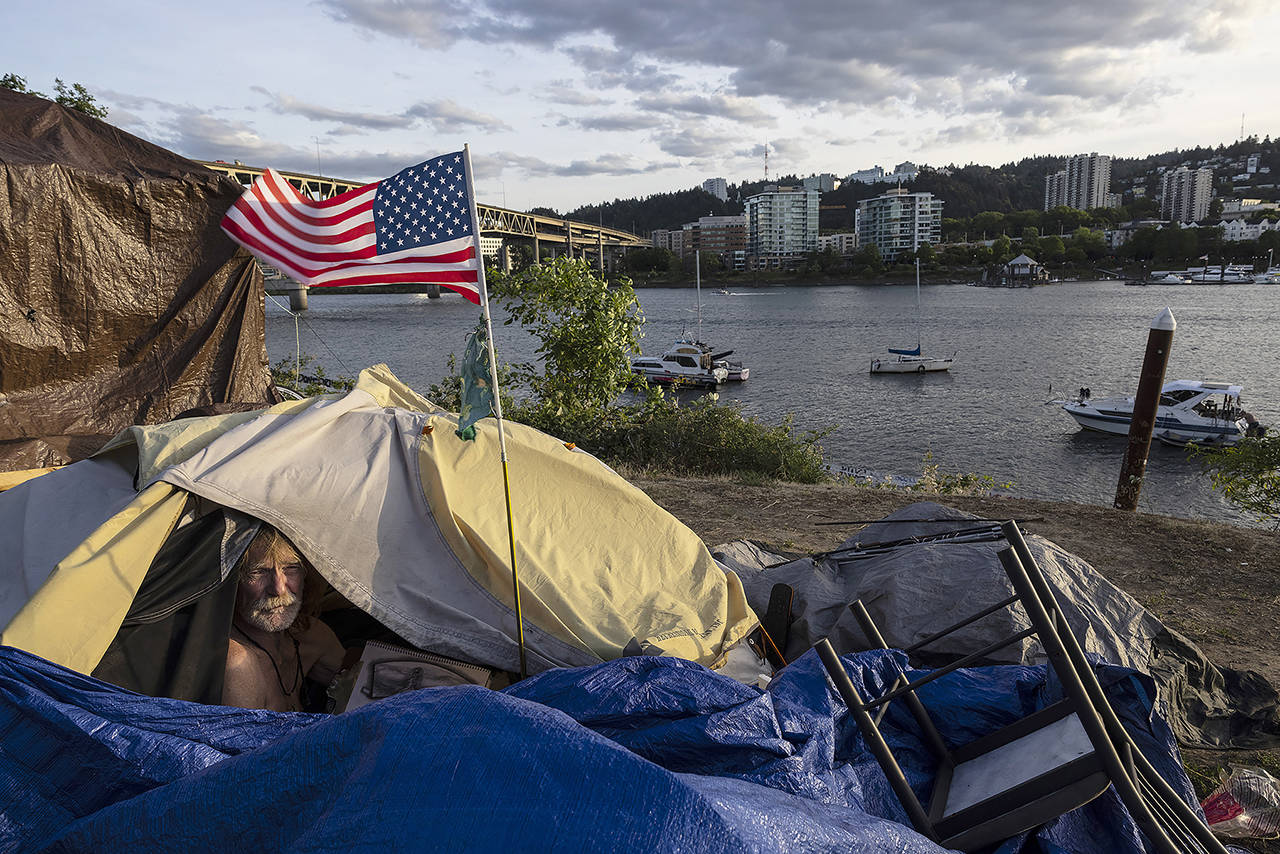 Frank, a homeless man, sits in his tent with a river view in Portland on June 5. (AP Photo/Paula Bronstein)