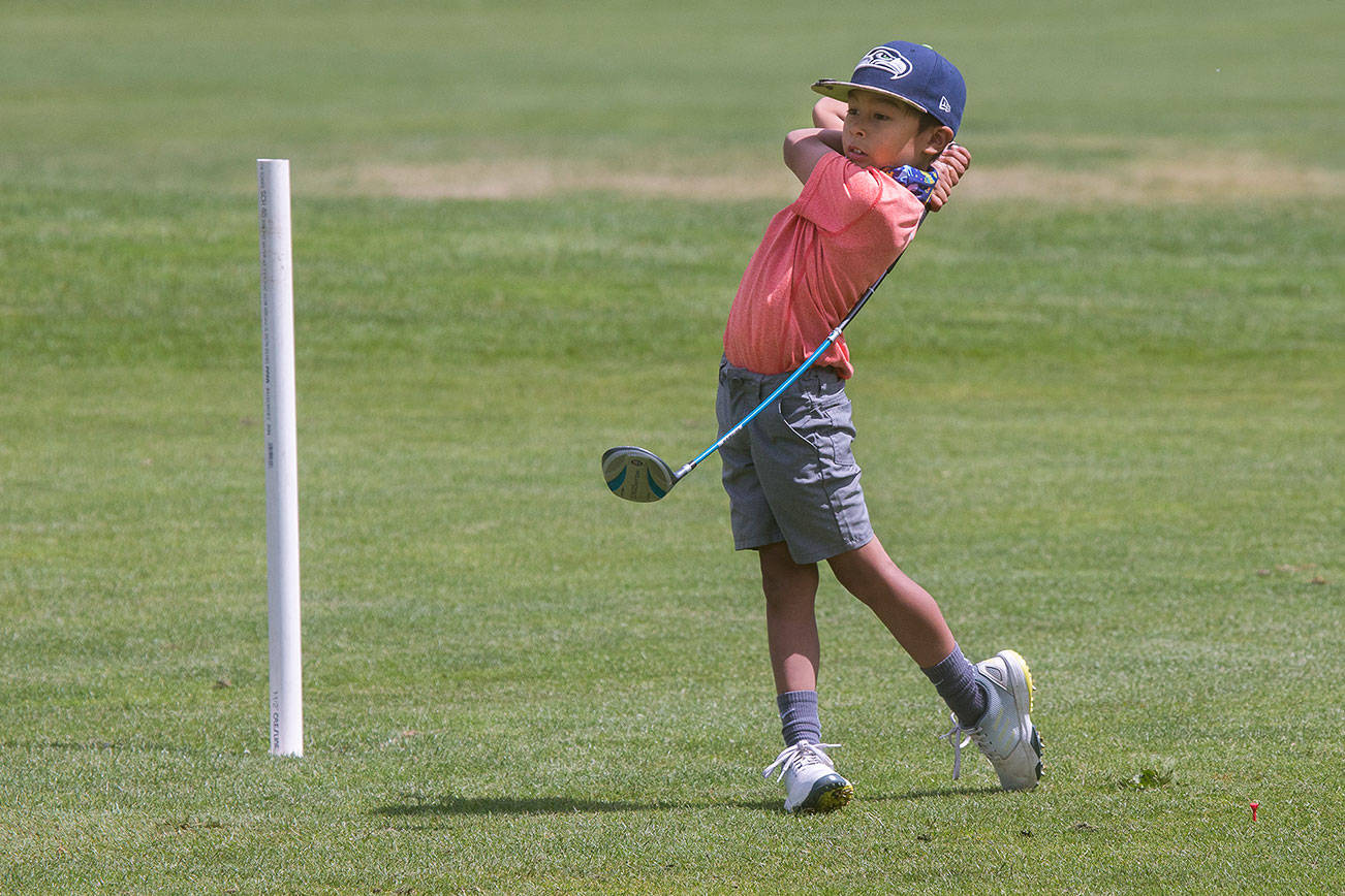 Barely taller than the 150yard marker,  Max Soterakopoulos, 6, tees off as he and his family golfs at Legion Memorial Golf Course on Tuesday, June 15, 2021 in Everett, Washington. Soterakopoulos hit a hole-in-one on the 14th hole at the golf course.  (Andy Bronson / The Herald)
