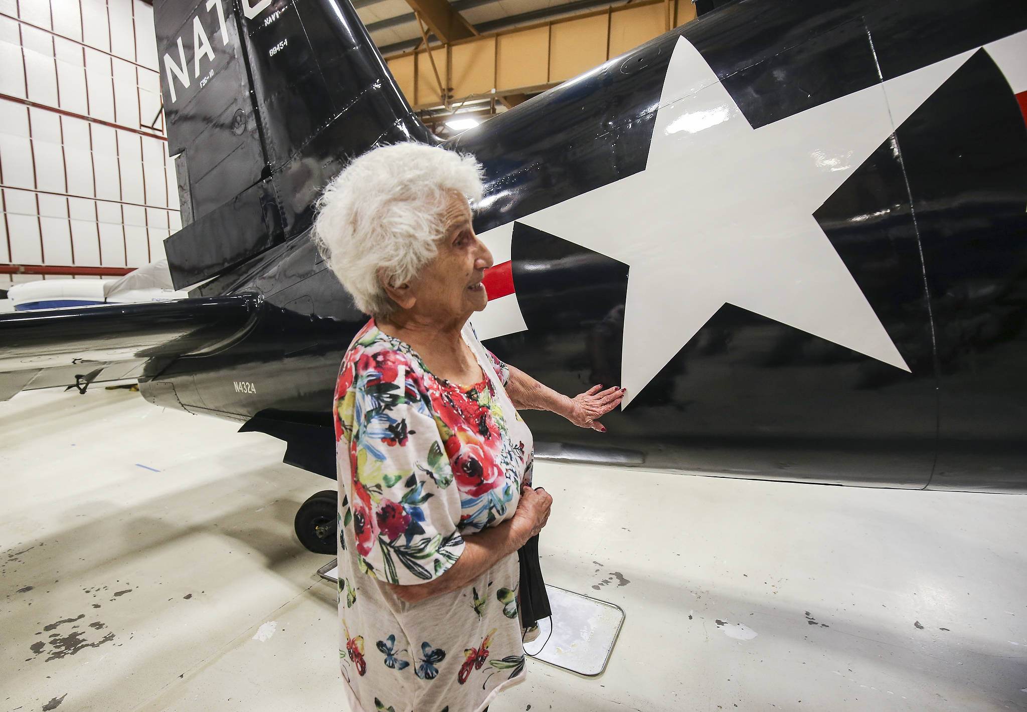 """Helen Mary Vaudrin, who was a """"Rosie the Riveter"""" at the Goodyear Aircraft plant in Akron, Ohio, during World War II, touches an F2G-1 Super Corsair at the Museum of Flight's Restoration Center & Reserve Collection at Paine Field on Wednesday in Everett. It is believed that she riveted the fuselage of the plane. (Andy Bronson / The Herald)"""