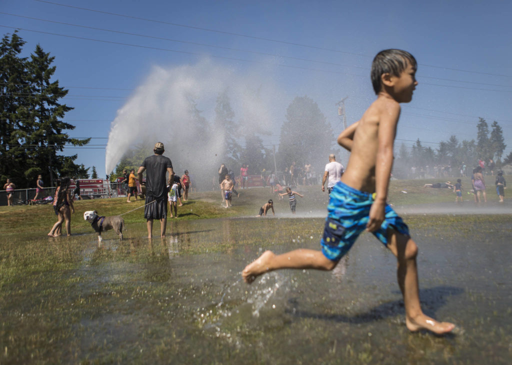 People enjoy the fire hose sprinkler station set up Saturday by the Everett Fire Department at Walter E. Hall Park in Everett. (Olivia Vanni / The Herald)