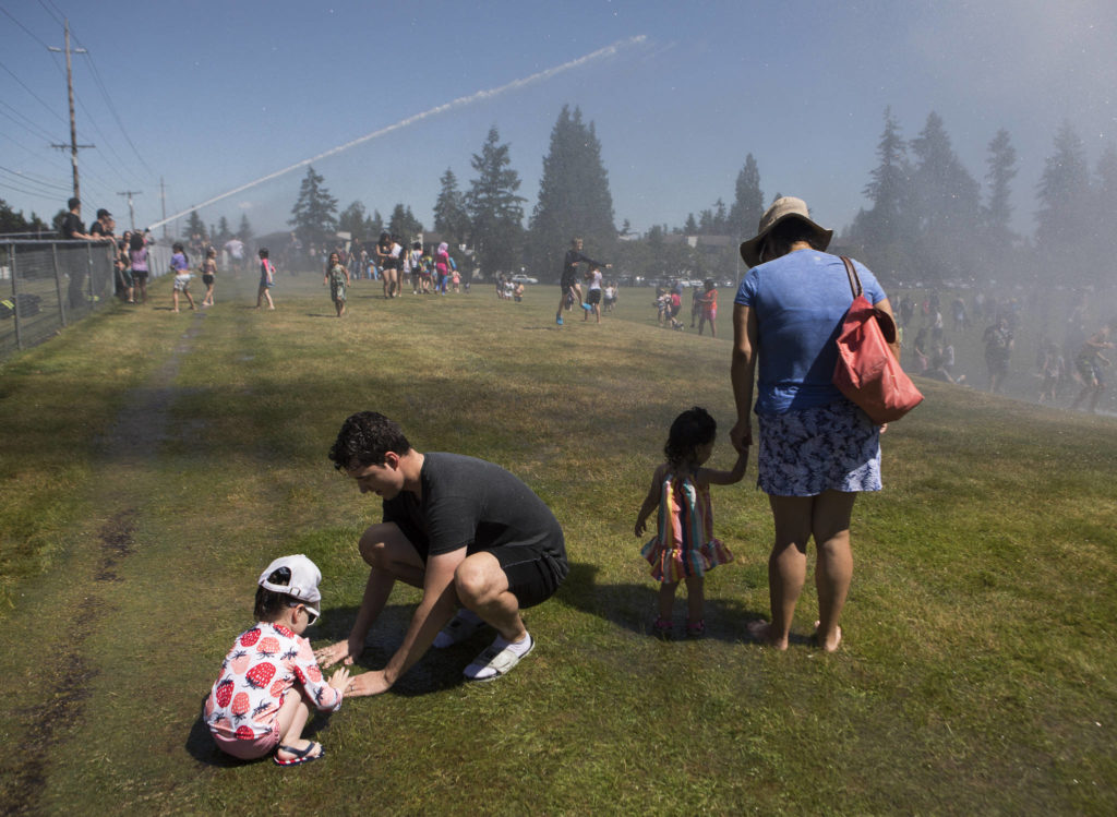 Derek Bock and his daughter Olivia, 3, left, play in a small puddle Saturday at the Everett Fire Department's fire hose sprinkler station at Walter E. Hall Park in Everett. (Olivia Vanni / The Herald)