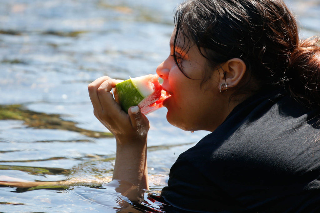 Cooling off in the Pilchuck River in Snohomish Monday. (Kevin Clark / The Herald)