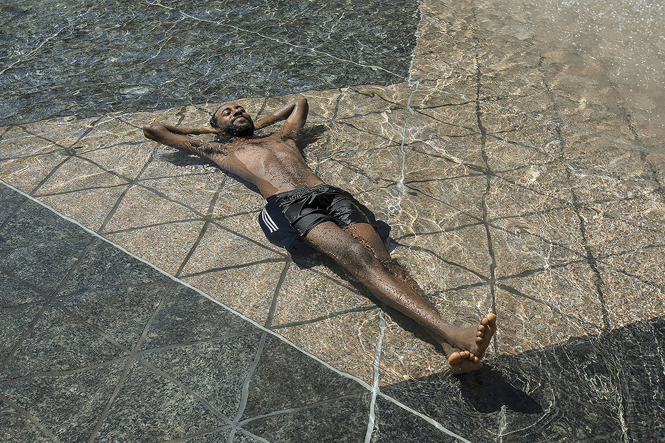 Kais Bothe relaxes in the cool in the city hall pool, as temperatures hit 37 degrees Celsius (98.6 Fahrenheit) in Edmonton, Alberta, on Wednesday, June 30, 2021. (Jason Franson/The Canadian Press via AP)