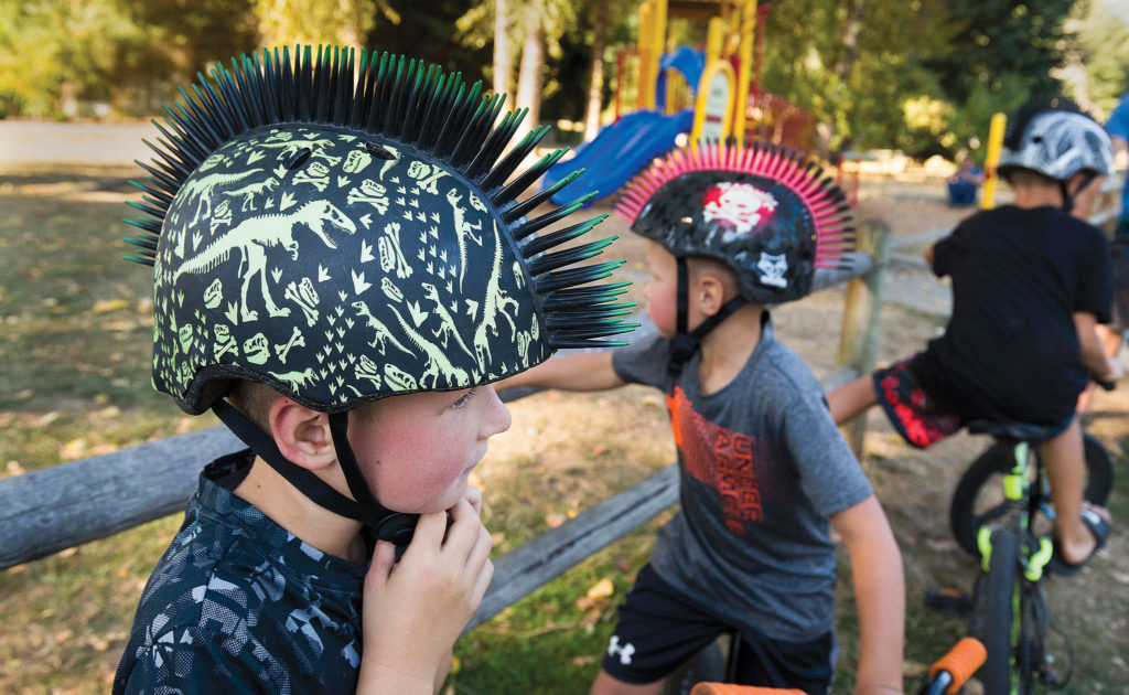 Brothers Cainan (left) and Cyles Winslow sport spiked helmets as they get ready to ride home with other family members from the Machias Trailhead. (Andy Bronson / The Herald)