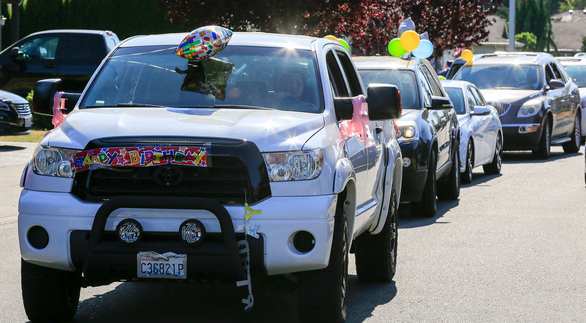 Cars line up to give Essie Klopfenstine drive-by birthday wishes and presents Tuesday afternoon in Marysville. (Kevin Clark / The Herald)