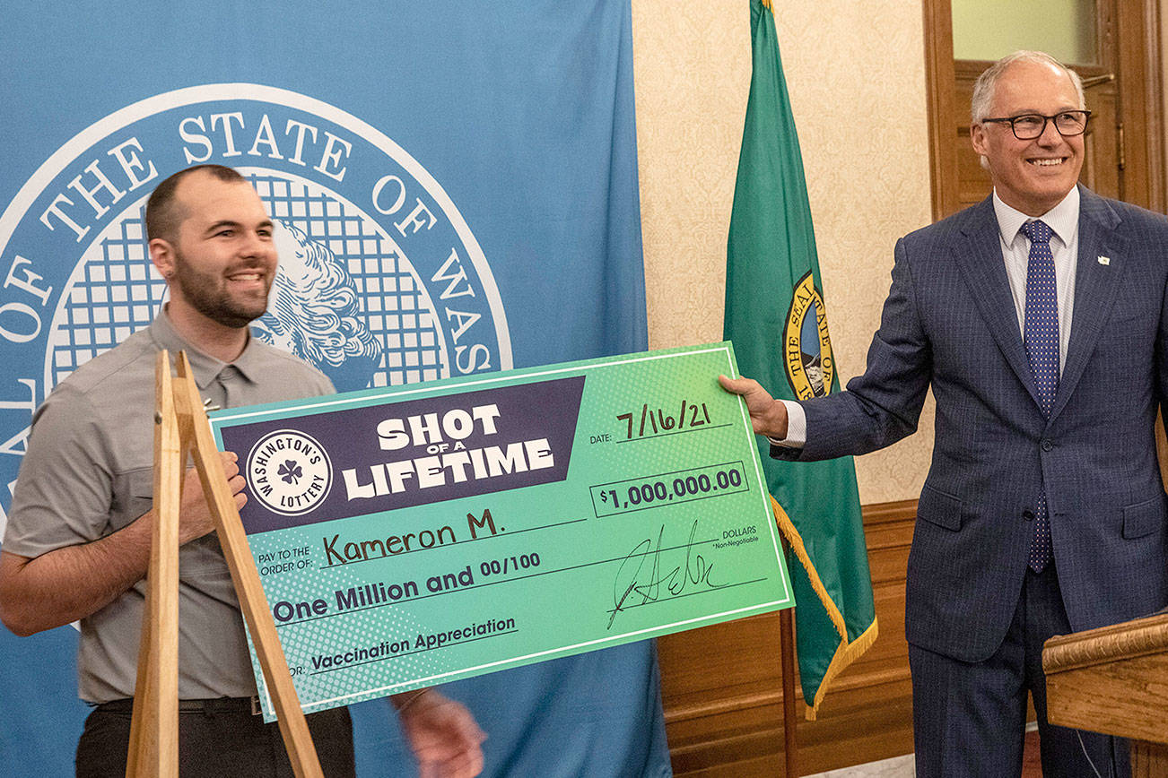 """Kameron M., 23, from South King County is all smiles at a press conference in Olympia, Wash., Friday, July 16, 2021, with Washington Gov. Jay Inslee, right, after accepting a mock check for $1 million, which he won as part of a """"Shot of a Lifetime"""" lottery open to all who got the COVID-19 vaccine. The motorcycle mechanic didn't know about the lottery but said he got his vaccine as soon as he could because he thought it was the right thing to do.  (Ellen M. Banner/The Seattle Times via AP)"""