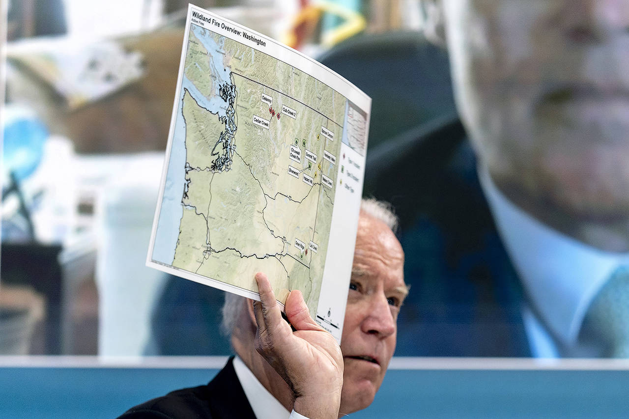 President Joe Biden holds up a map of wildfires in Washington state as he speaks with governors about efforts to strengthen wildfire prevention, preparedness and response, and hear firsthand about the ongoing impacts of the 2021 wildfire season, on Friday in Washington D.C. (AP Photo/Andrew Harnik)