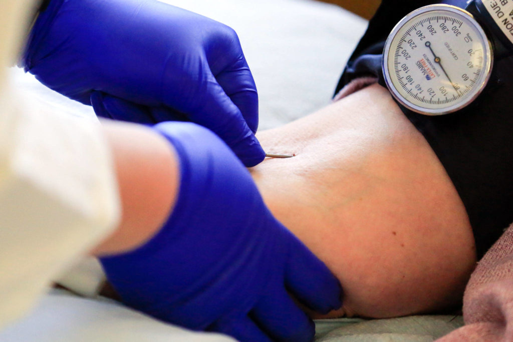 JaNeen Aagaard donates blood at Bloodworks Northwest on Friday in Everett. (Kevin Clark / The Herald)